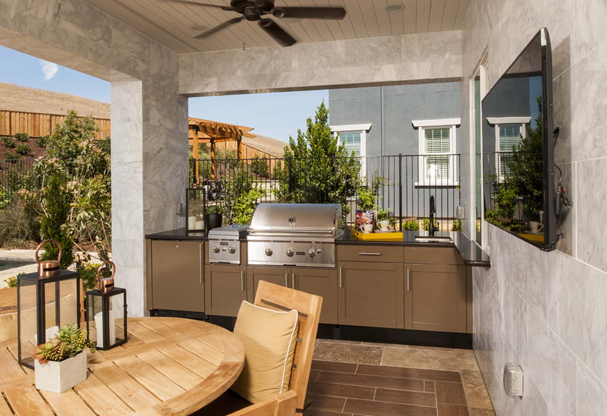 covered outdoor kitchen tiled walls wood ceiling stainless grill tan cabinets