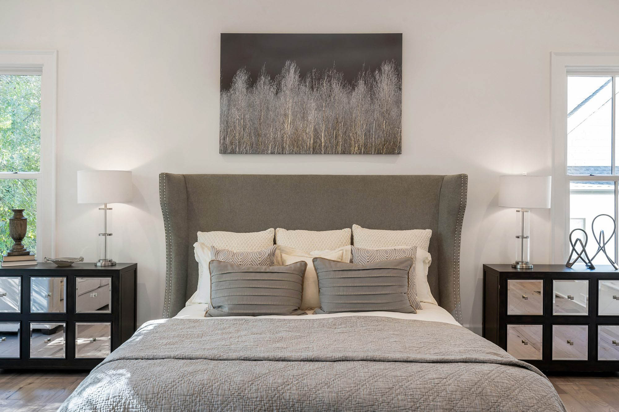 plush gray headboard with gray pillows and comforter black end tables white lamps