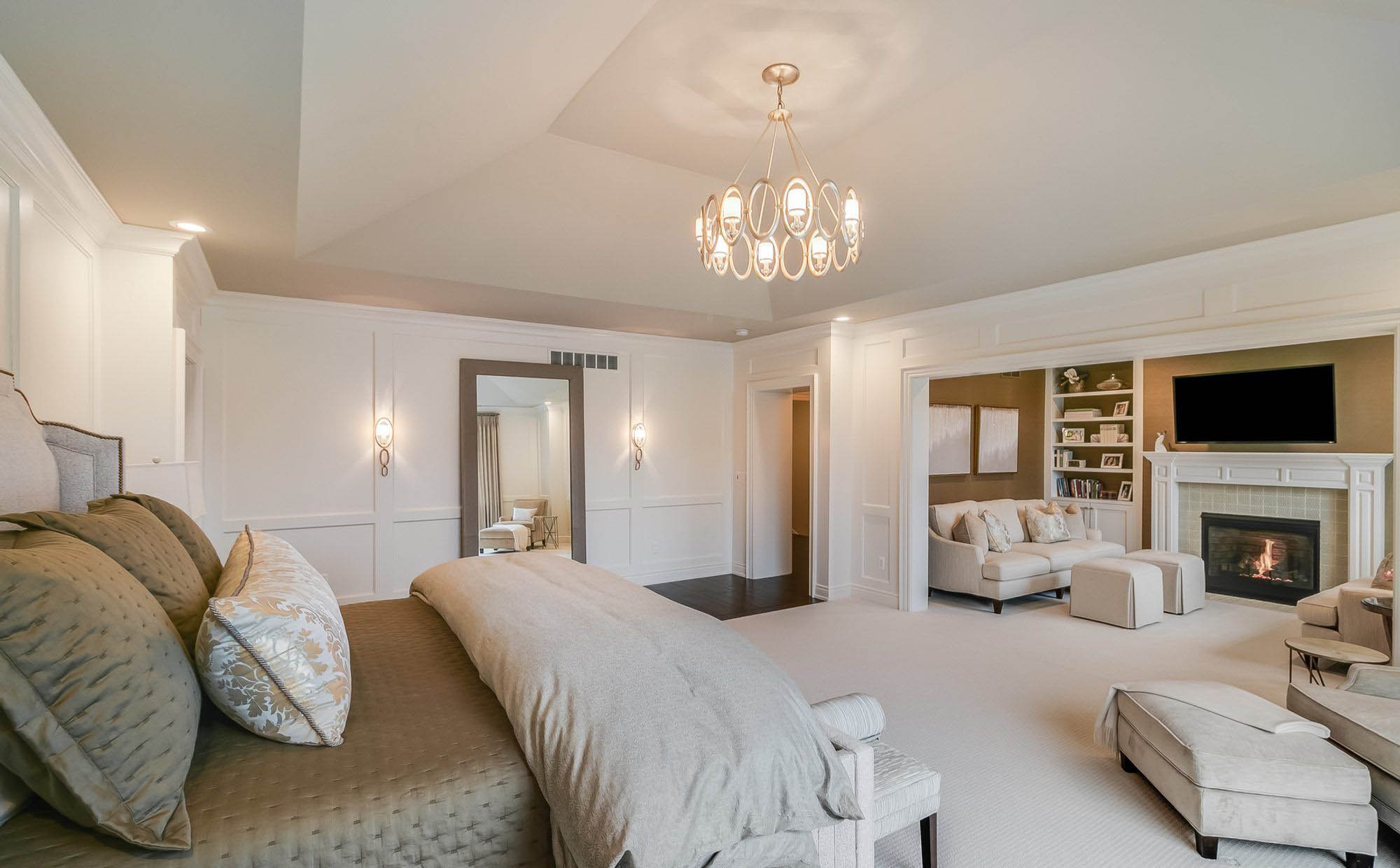master bedroom with sitting room white wall paneling chandelier dark hardwood floors fireplace surround