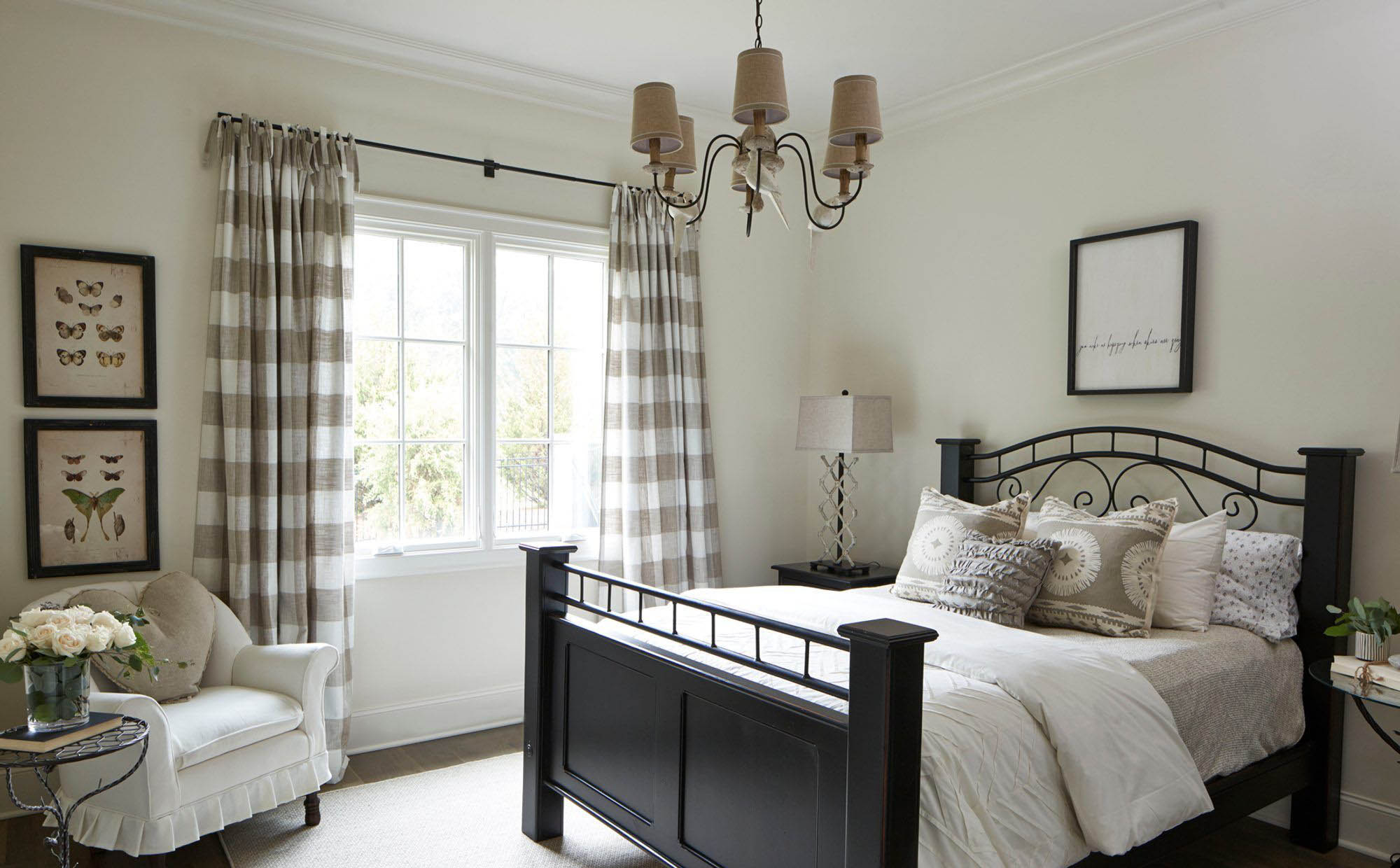 small master bedroom design black bed r=frame with cream and white bedding cream walls checkered drapers