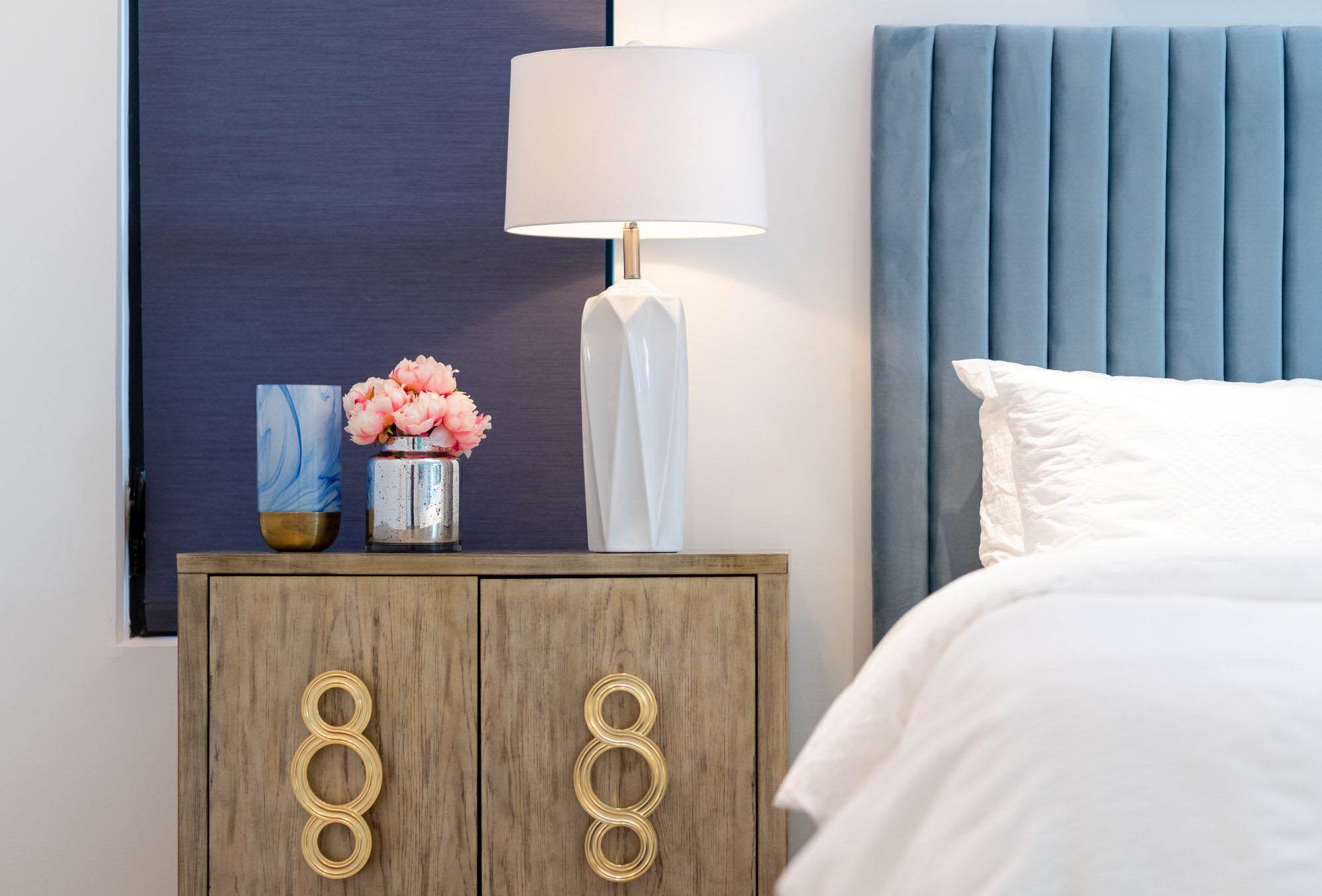closeup view of a colorful bedside table blue plush headboard white bedding
