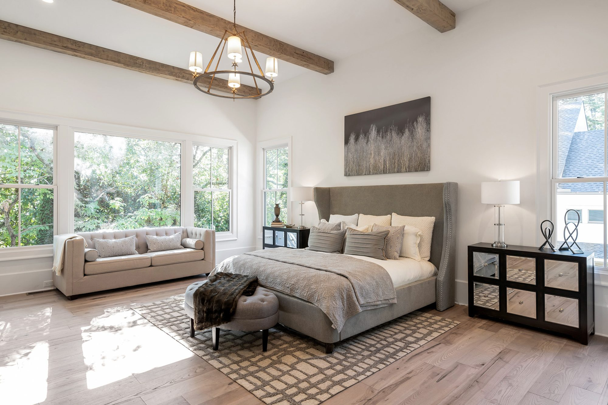 gray and cream master bedroom plush gray headboard area rug dropped wood beams hardwood floors