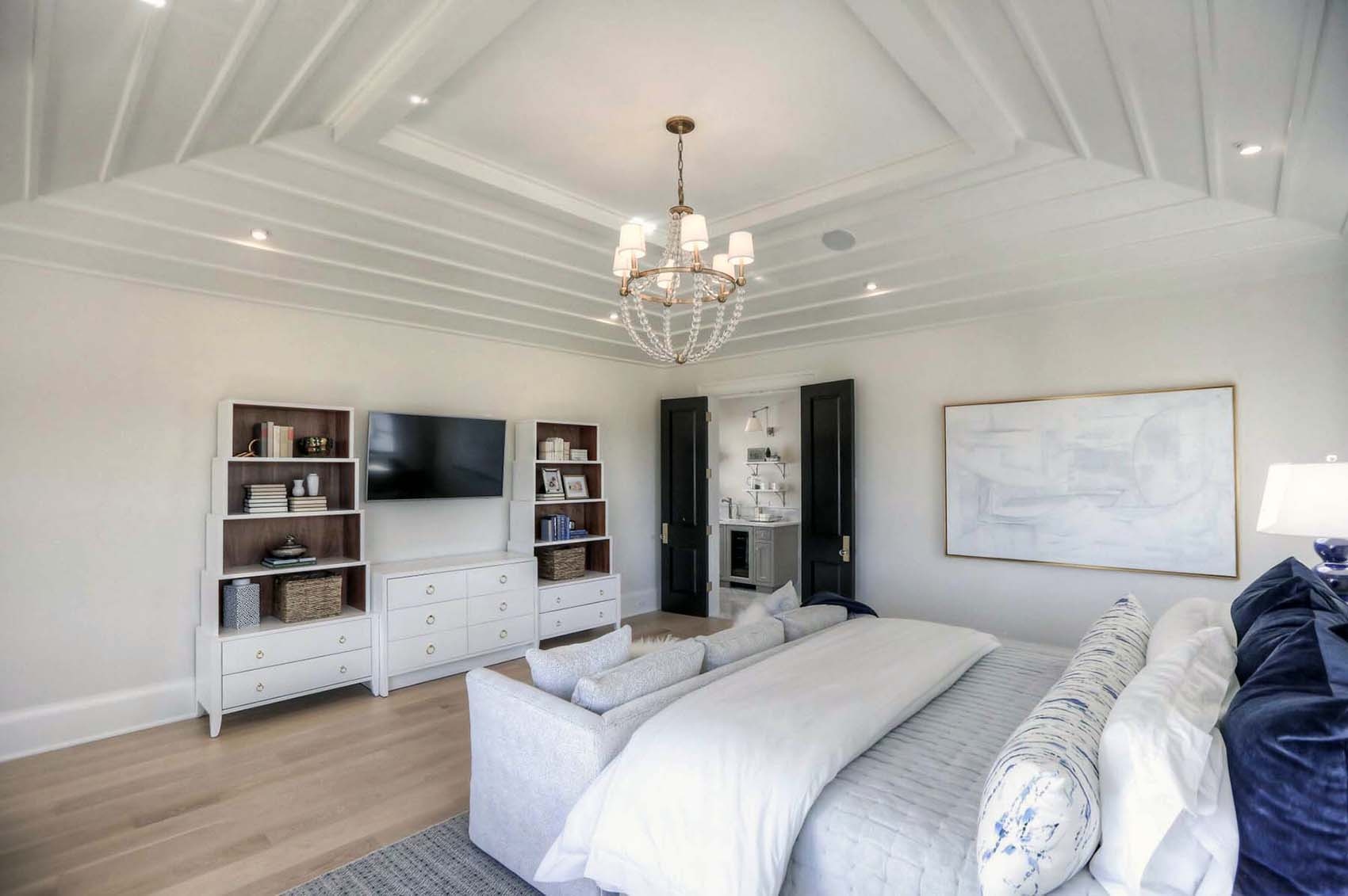 master bedroom with custom vaulted ceiling and chandelier