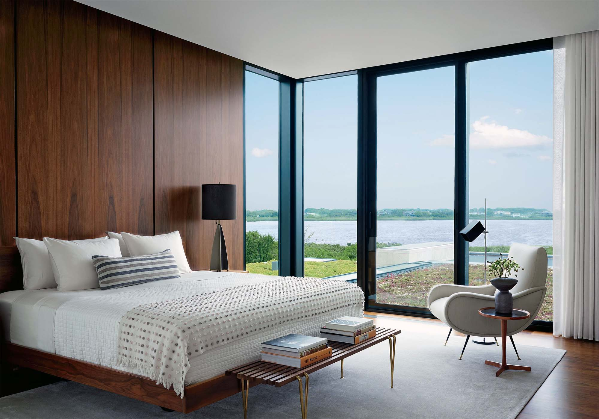 modern master bedroom design with wood walls matching bed frame area rug floor to ceiling windows