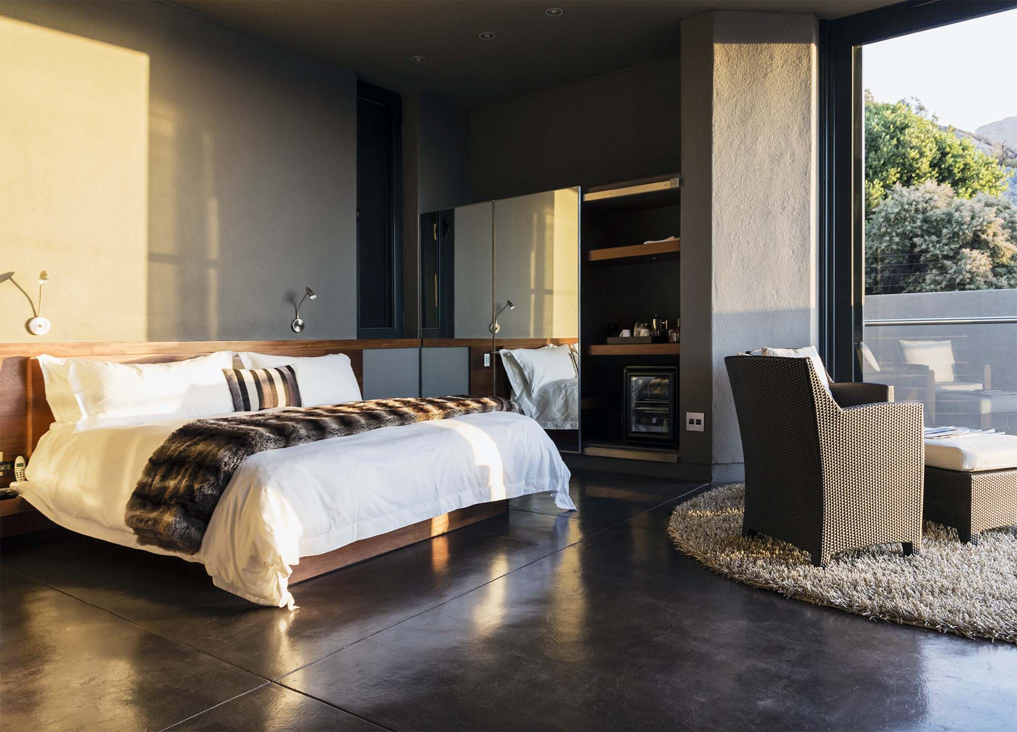 ultra modern master bedroom design with polished concrete floors gray walls floor to ceiling windows and doors