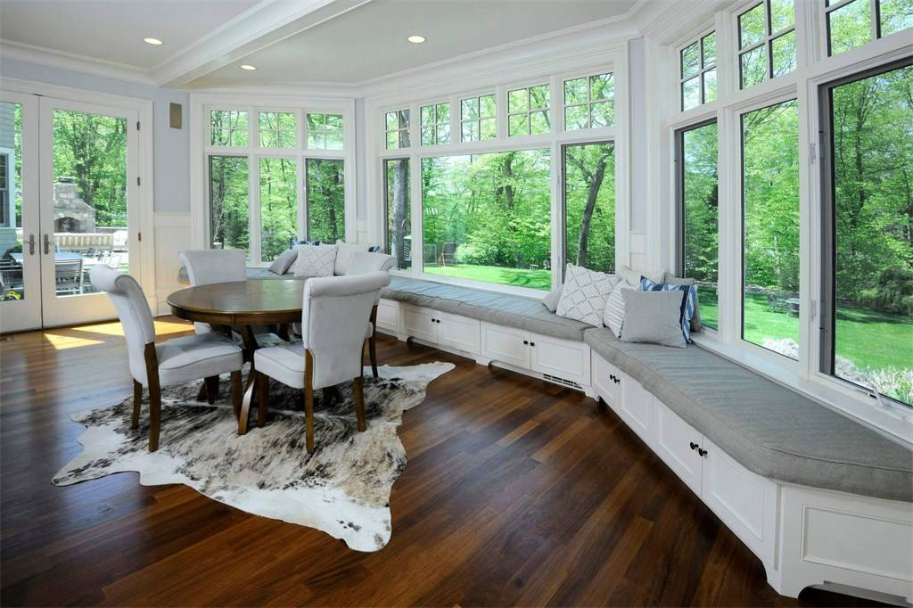 beautiful custom sunroom addition white and gray with wood floors and animal rug