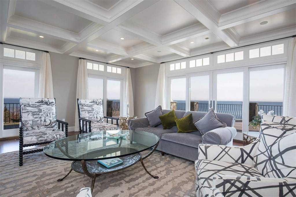 oceanfron sunroom with coffered ceilings and floor to ceiling windows