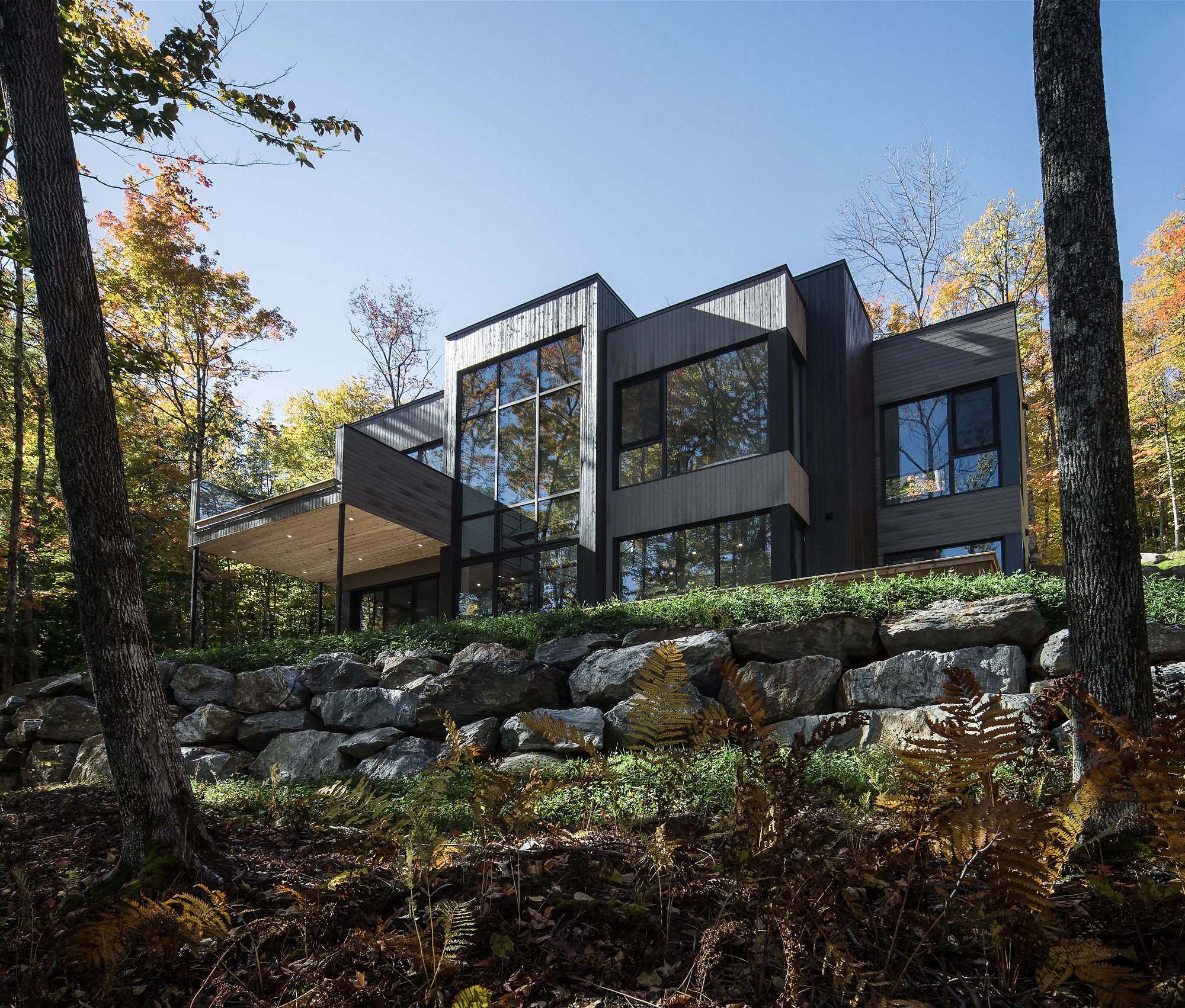 Modern home with ipe siding. Real stone boulders. Flat roof design. - Gambrick