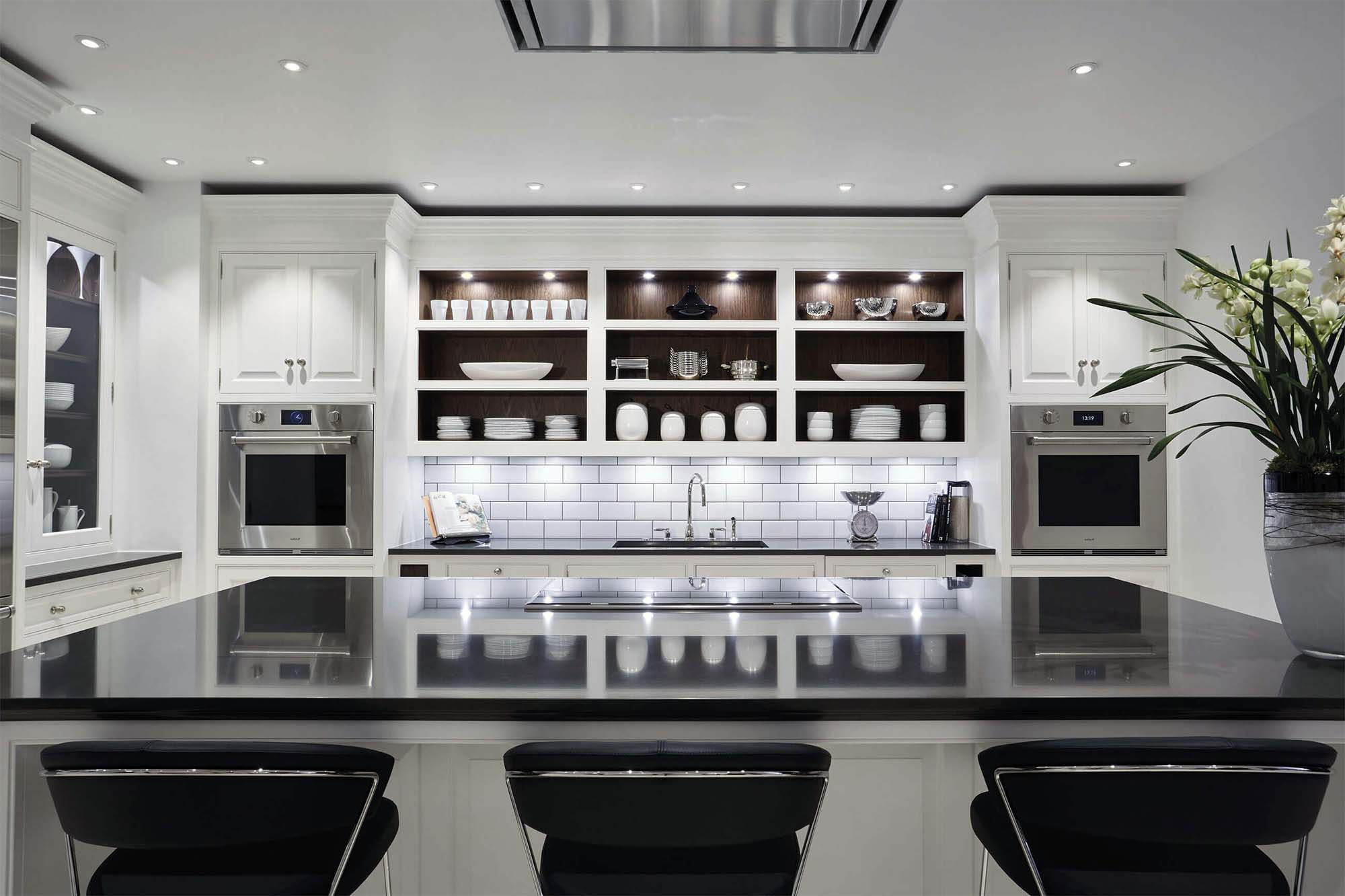 high end appliances in a luxury white kitchen with black quartz countertops