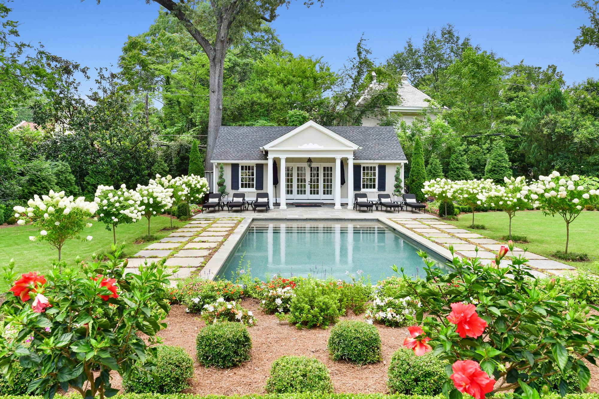 classic Hamptons style pool house design with cream siding, white trim and blue shutters