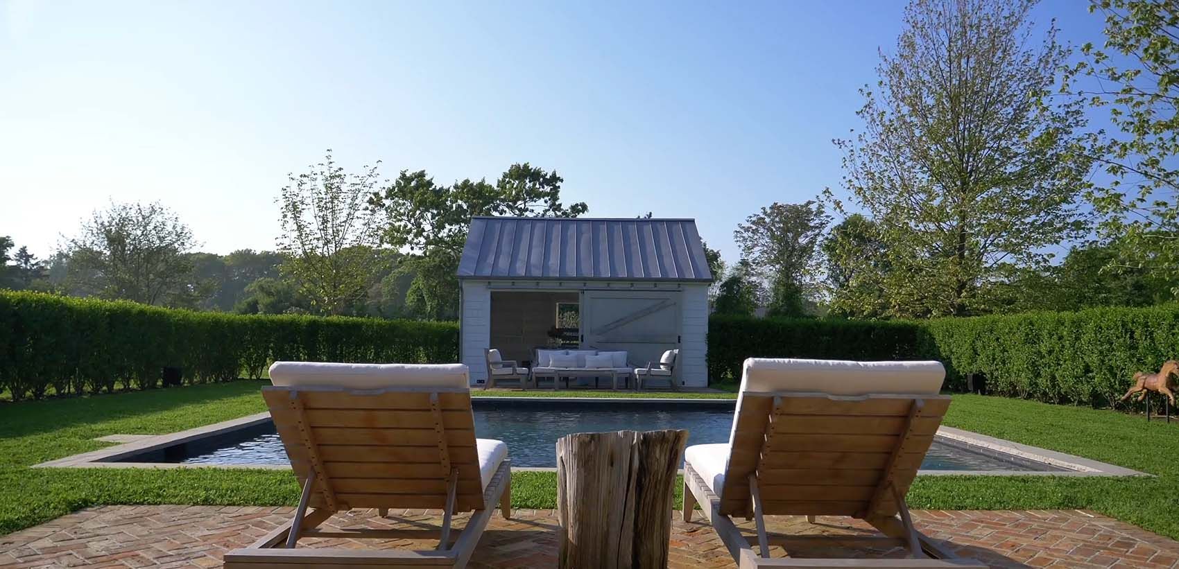 Tiny pool house design with shed doors white siding and metal roof