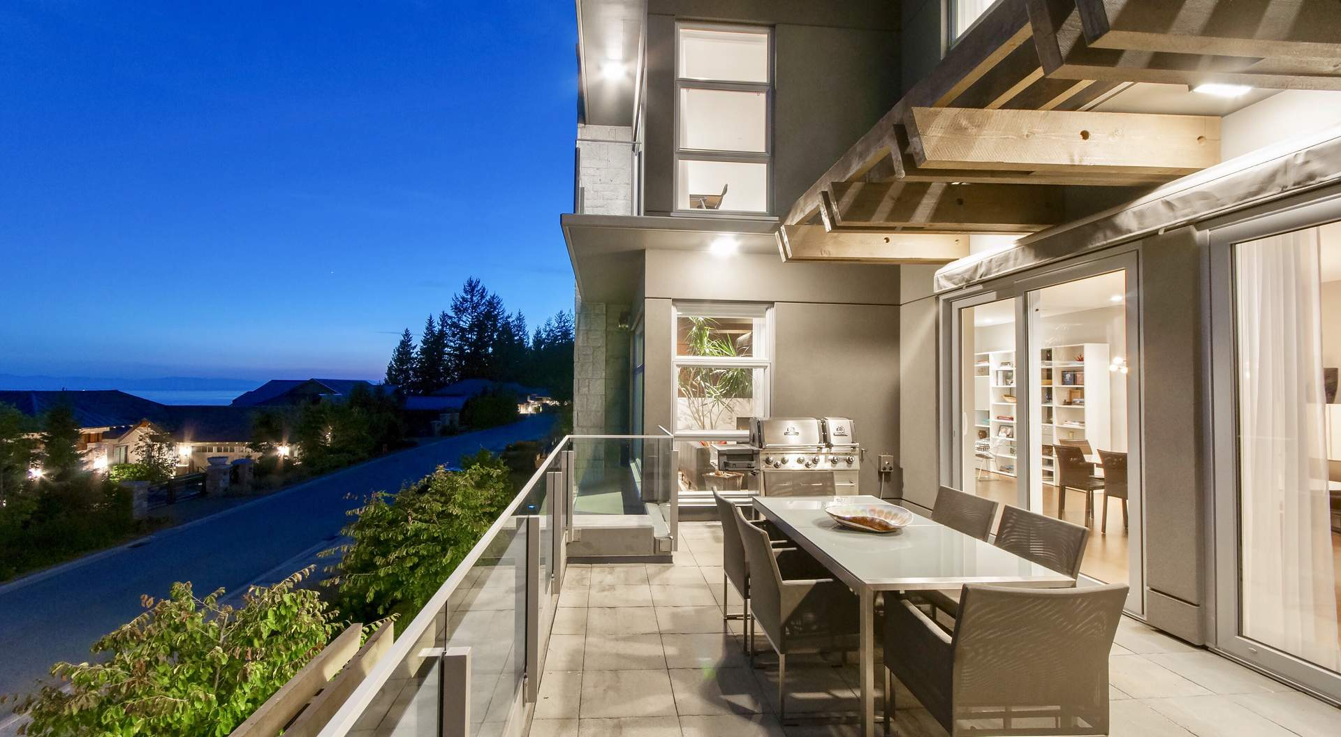 modern home builder - open balcony with stone tile floors, glass rails, exposed beams, stucco finish