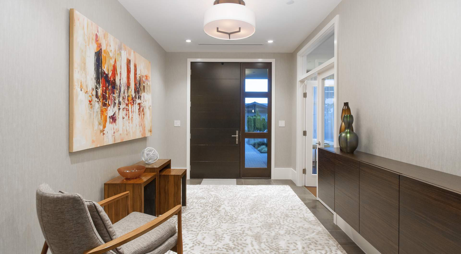 contemporary home builder - entry with modern dark wood front door, single sidelight, gray tiles with light patterned area rug