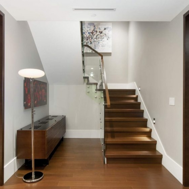 modern wood stairs with glass railings, wood floors and door trim, large white base trim