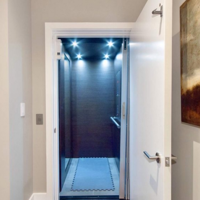 Contemporary home elevator, white door with brushed hardware, brown wood walls with tile floor, LED lighting