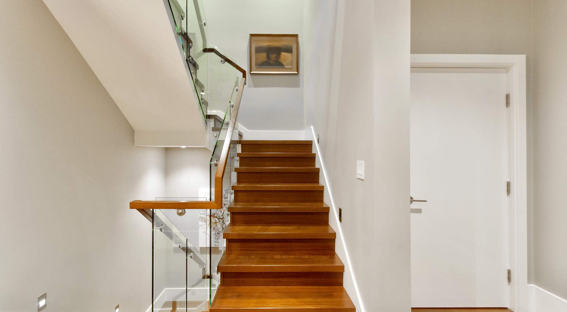 Contemporary stair design, wood treads and risers with modern glass railings and wood hand rail