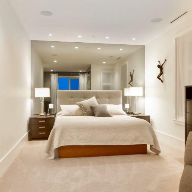 Contemporary bedroom design, tan rugs with white walls, ceilings and trim, huge wall mirror, LED lighting