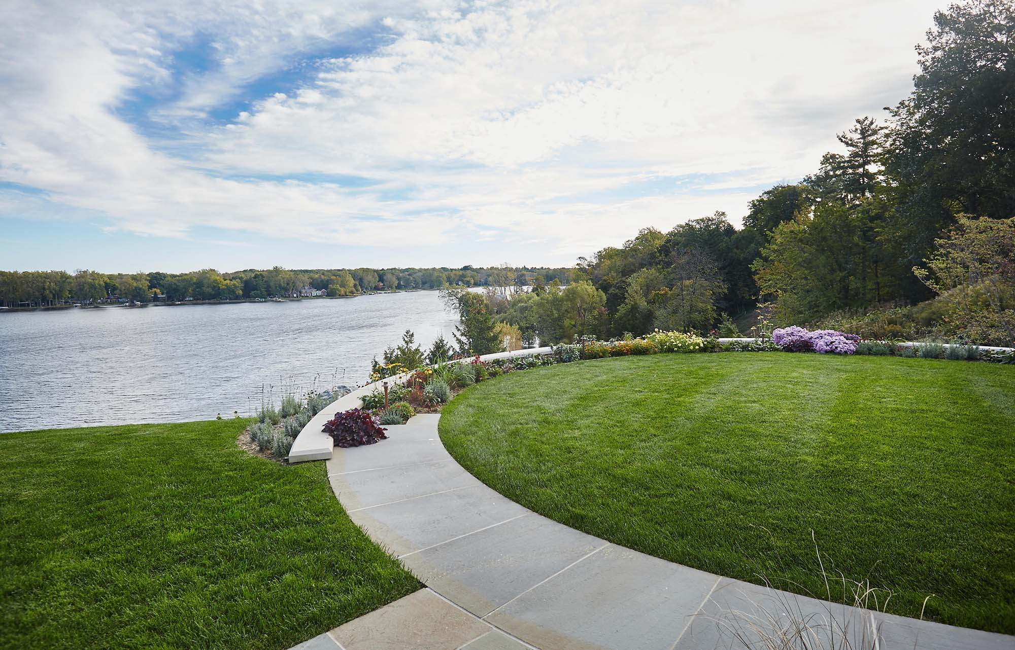 waterfront landscaping round bluestone and concrete patio