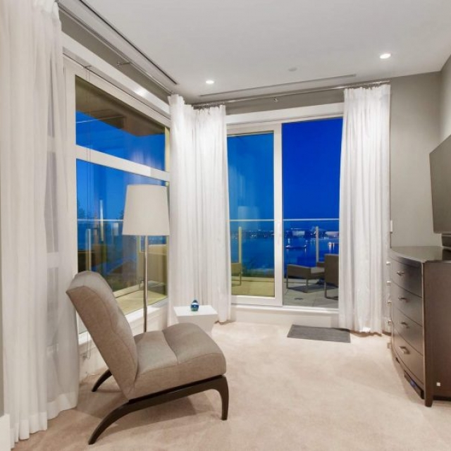 Bedroom sitting area, TV and chair, tan rugs, glass walls, modern balcony with glass railings, water views