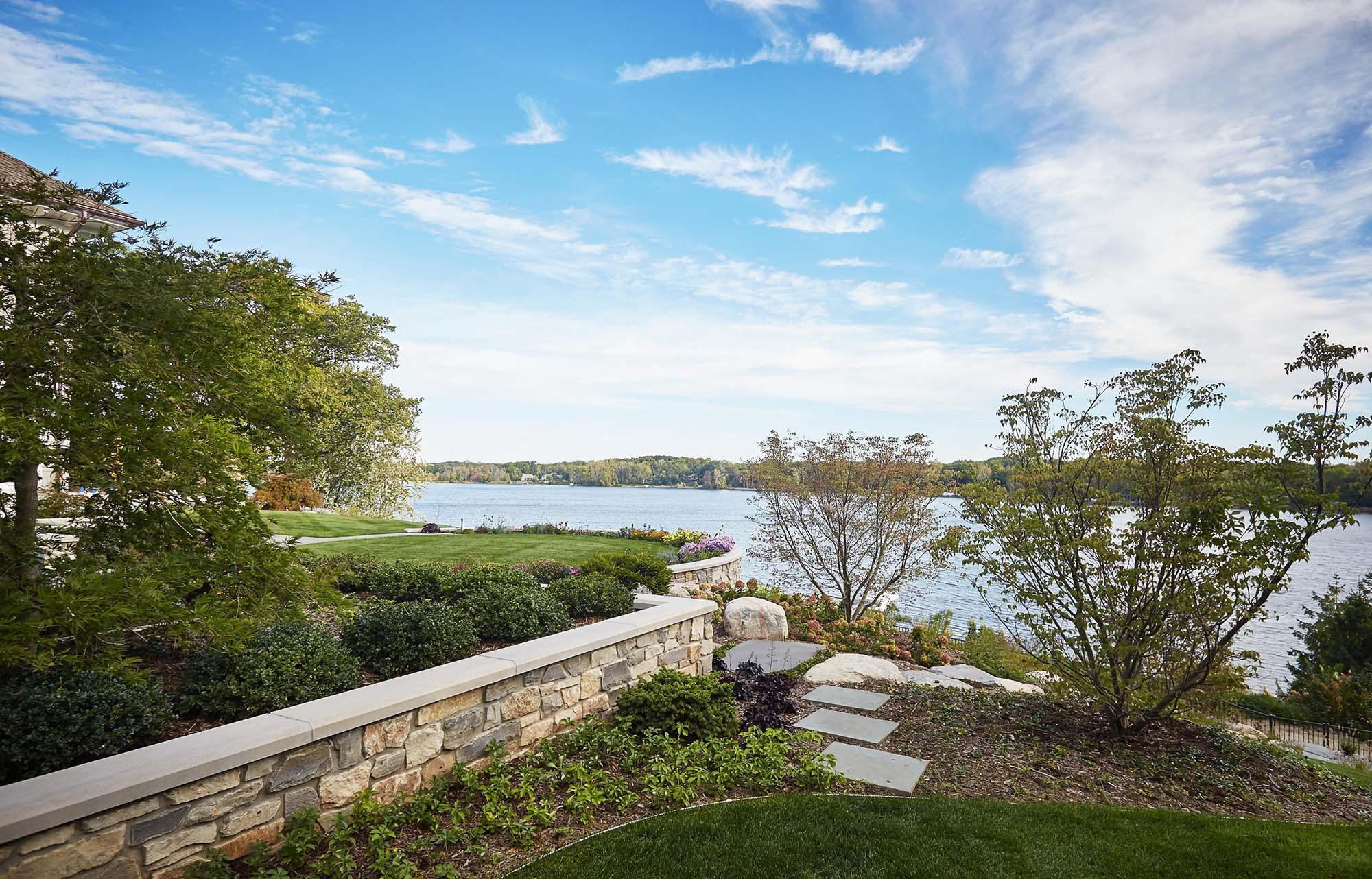 waterfront real stone retaining wall with concrete cap and beautiful landscaping