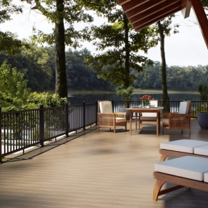 NJ lakefront Trex deck with black metal railings Wood patio furnite white cushions