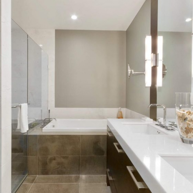 Modern bathroom with soaking jacuzzi tub, glass shower, his and hers sinks, white granite