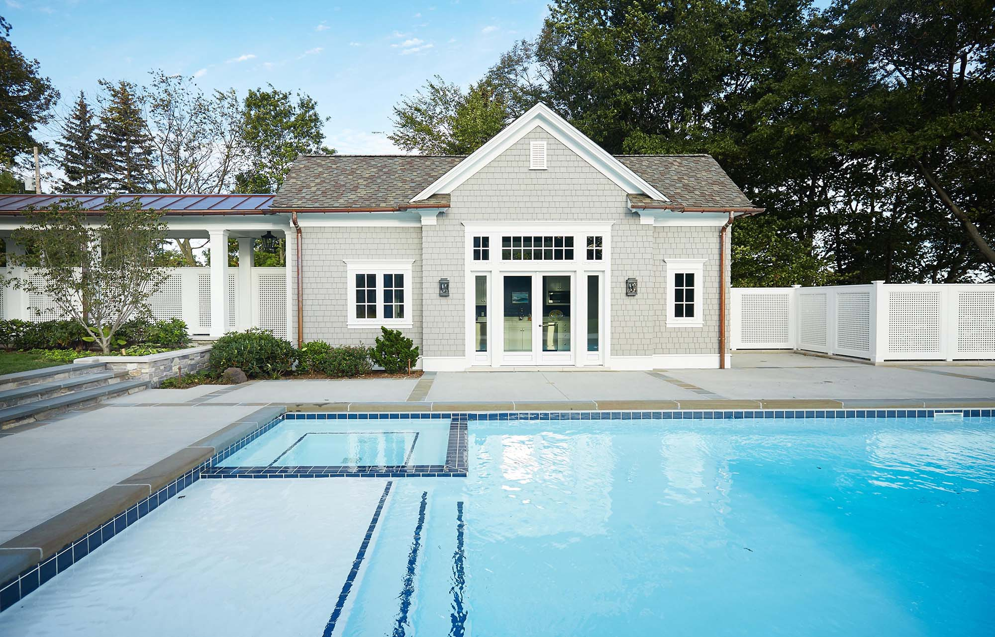 custom home builder NJ pool house with covered walkway and in ground pool