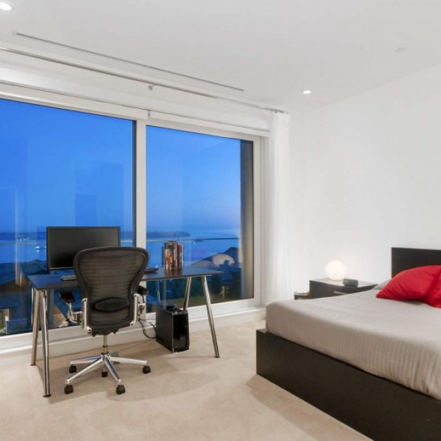 contemporary bedroom, dark wood bed frame with built in drawers, red throw pillows, glass wall, water views