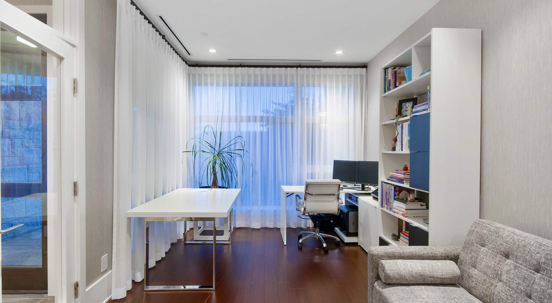 Modern home office, dark wood floors, white furniture, white and chrome desk, gray sofa glass walls.