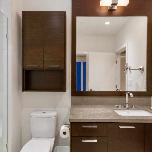 modern bathroom, dark wood vanity, large mirror with wood frame, chrome fixtures,