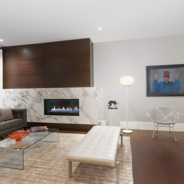 Modern gas fireplace with huge marble surround, medium dark wood floors with area rug, glass coffee table