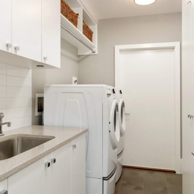 laundry room with white cabinets and white porcelain tile backsplash, white washer  dryer
