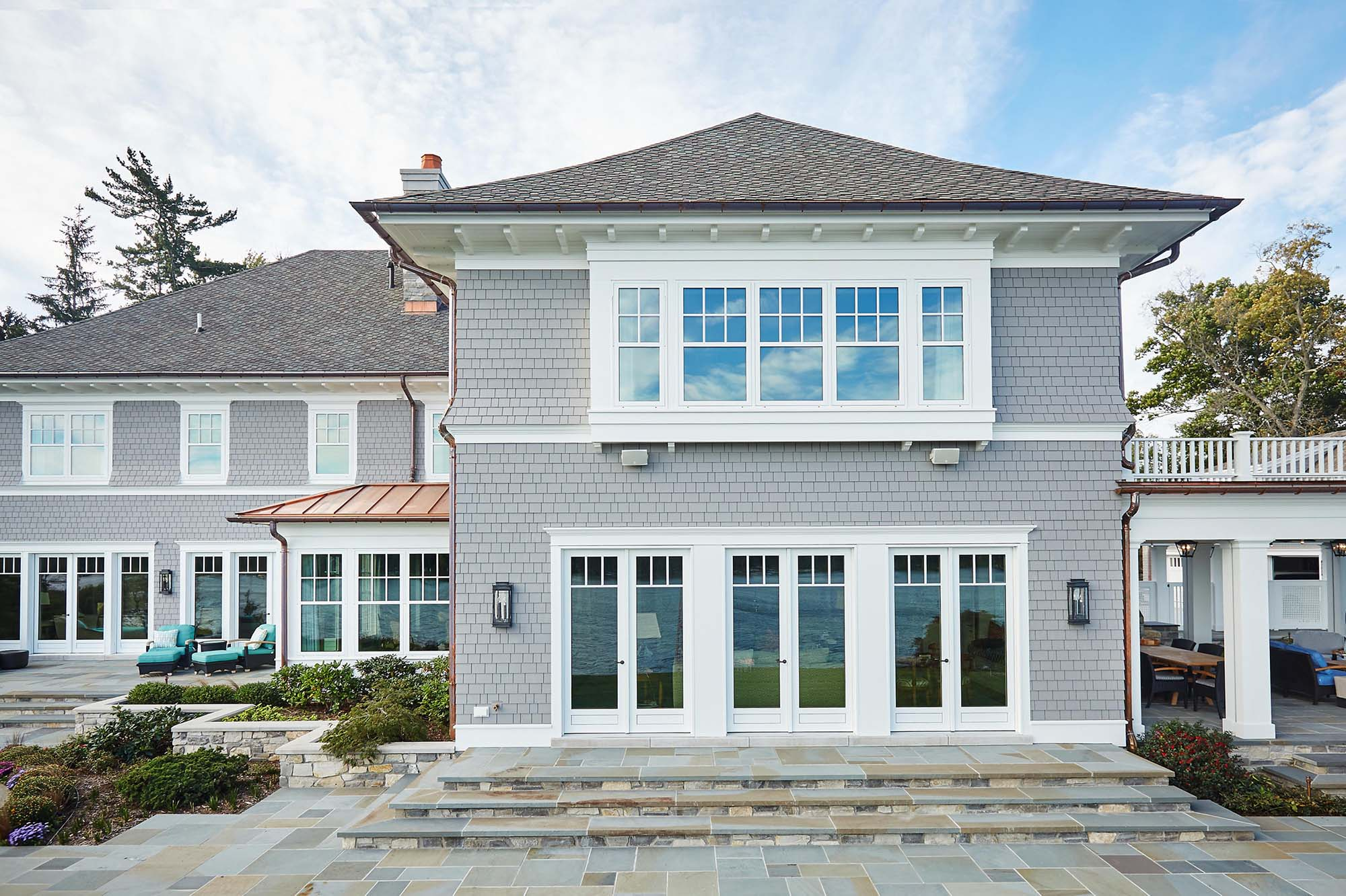 custom luxury home NJ rear view gray shake with white azek copper accent roof and gutters bluestone patio