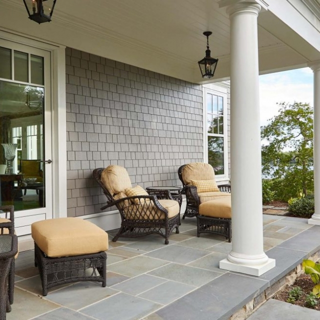 covered porch water views bluestone patio round columns gray siding with white azek copper gutters