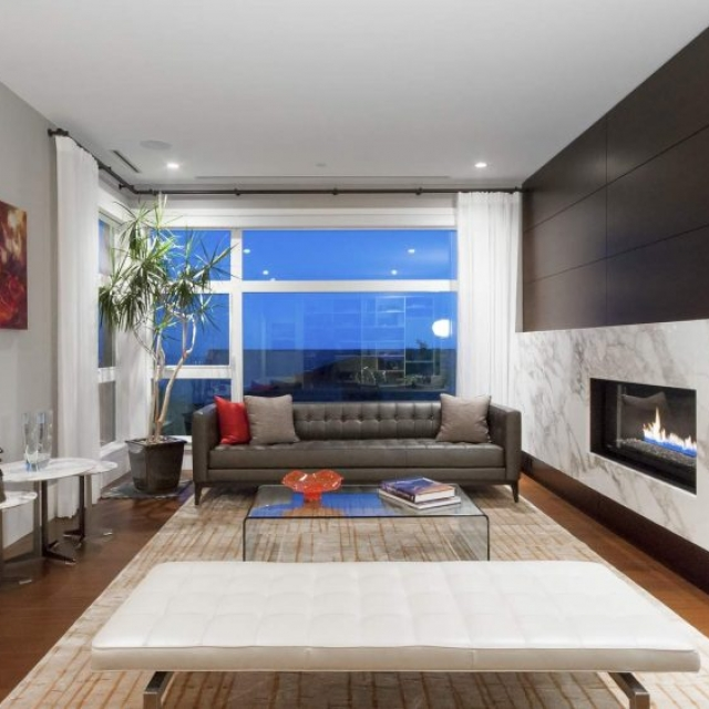 Modern living room, medium dark wood floors, modern fireplace with huge marble surround, gray walls