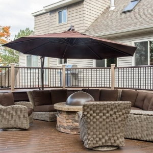 NJ Custom trex deck with curved design, stone fire pit, wicker furniture with brown cushions and umbrella, brown railings, multi level deck