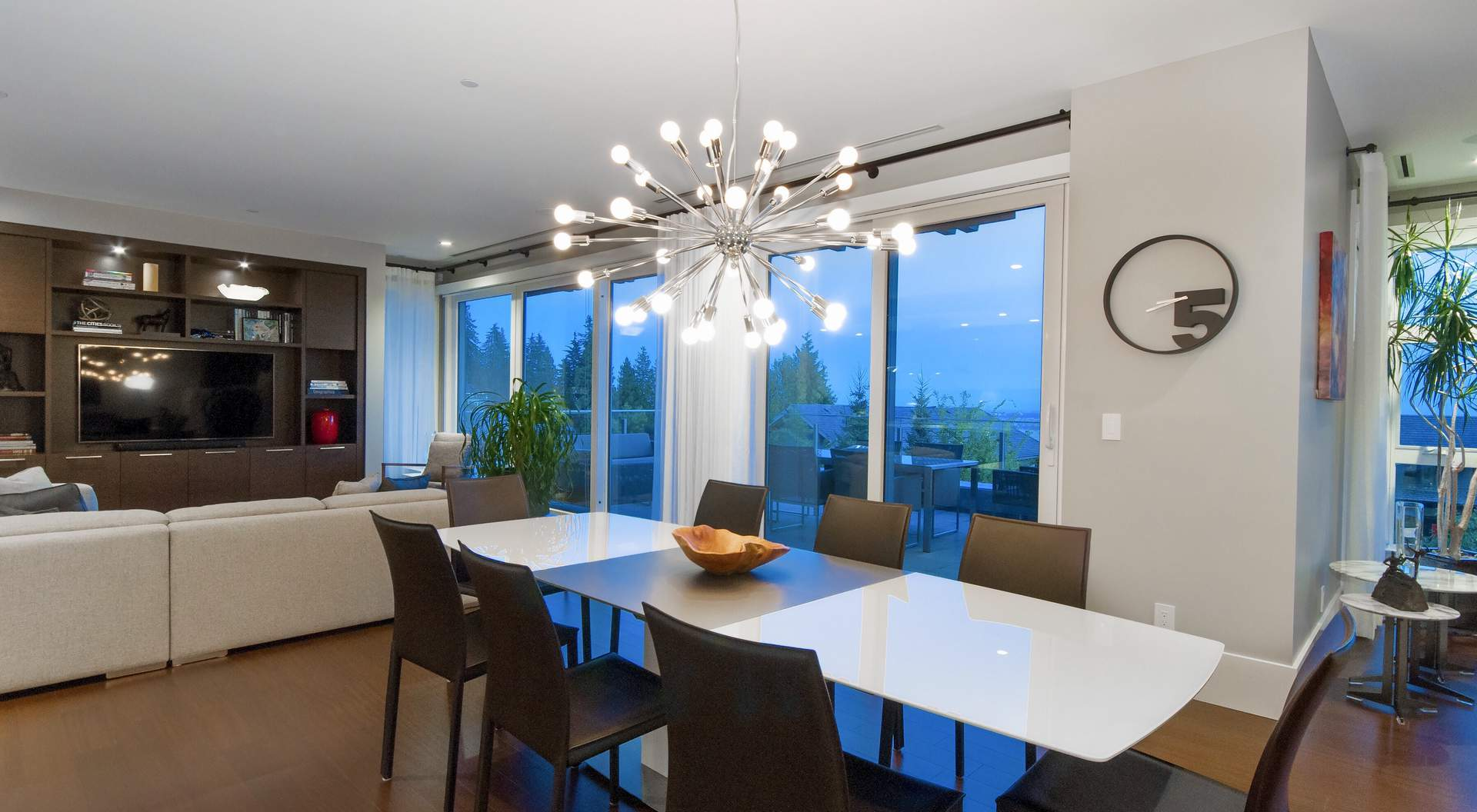 Modern open floor plan, modern chandelier, glass walls, gray walls, white kitchen table