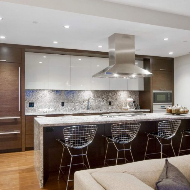 Modern home builder - kitchen - stone backsplash and island, stainless hood, wood cabinets and built ins