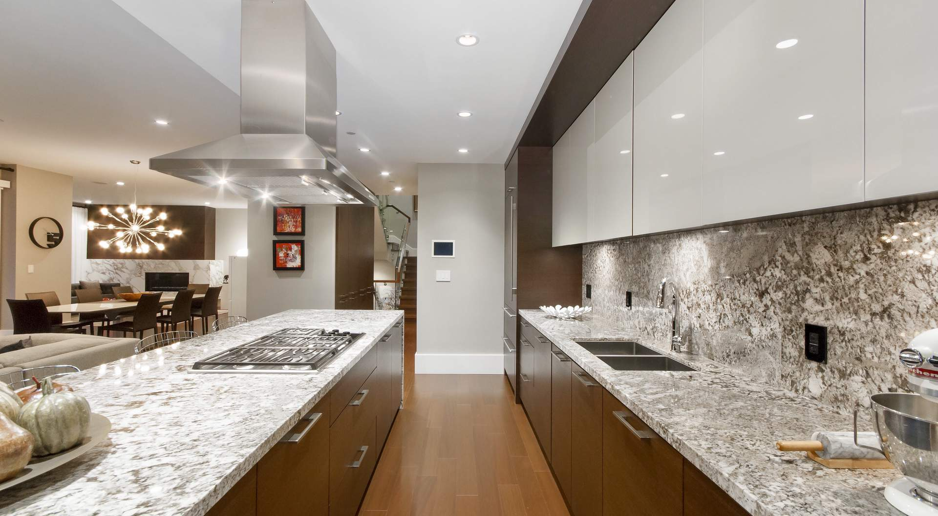 Modern home builder - kitchen - matching stone counters and backsplash, stainless steel, medium wood and white cabinets