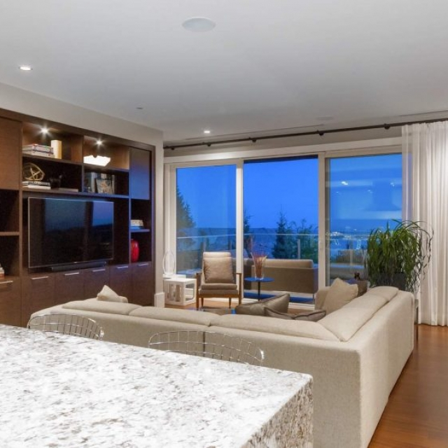 modern home builder - glass walls with water views, plush tan sofa, wood built ins