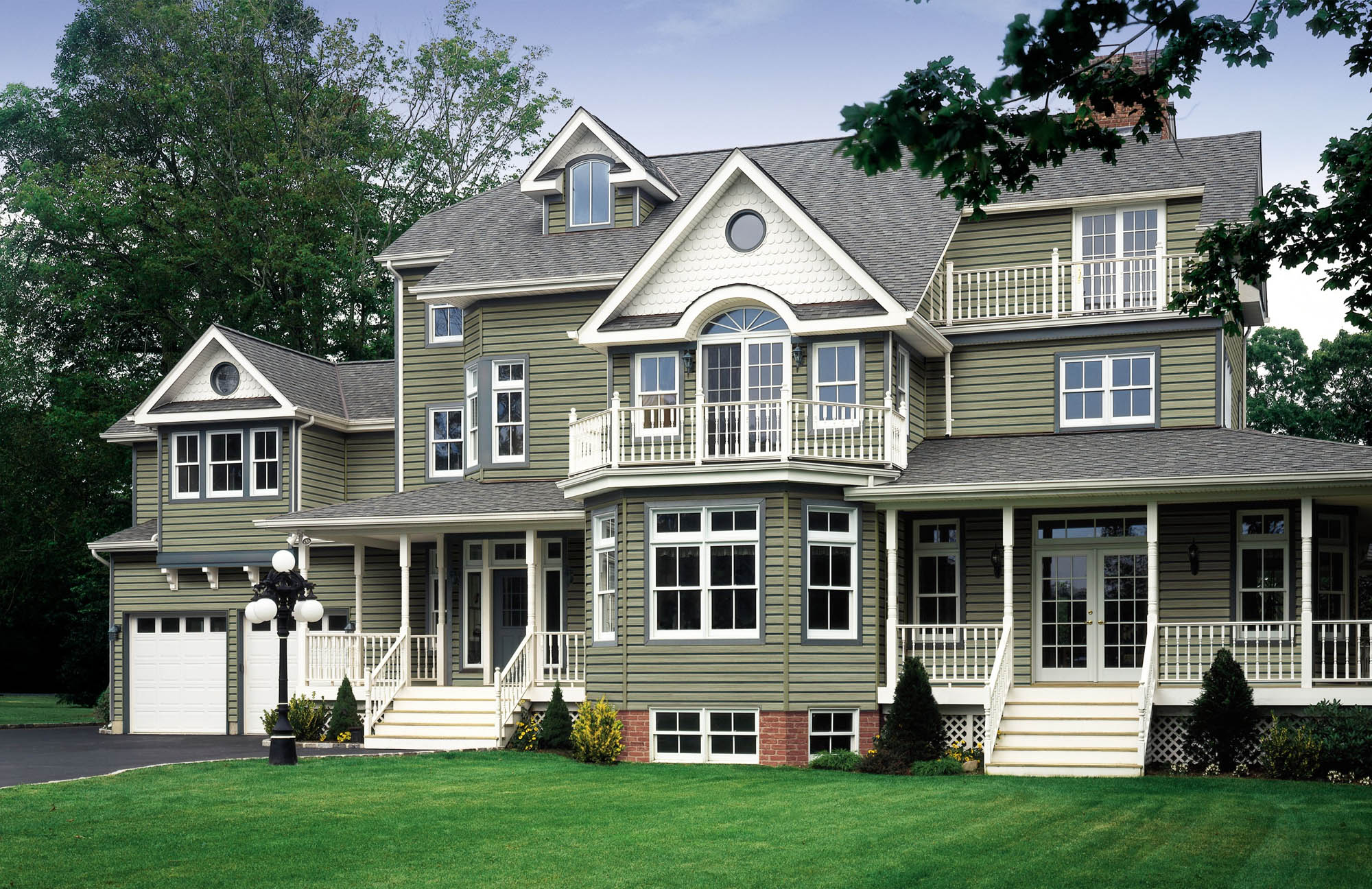 green house siding color ideas - green siding with brick white scalloping white railings and columns