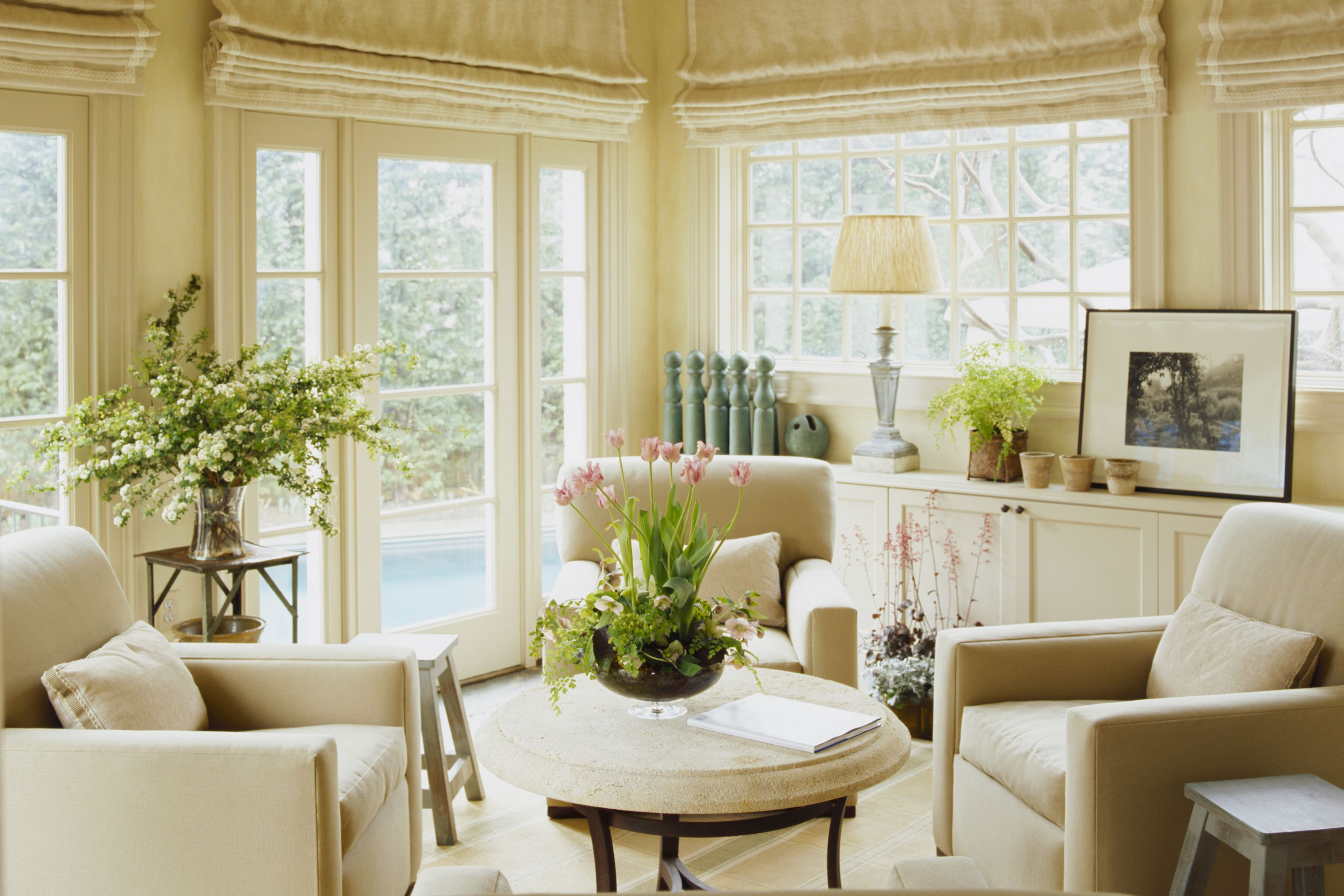 cream colored sunroom with roll down drapes built in cabinets cream plush chairs