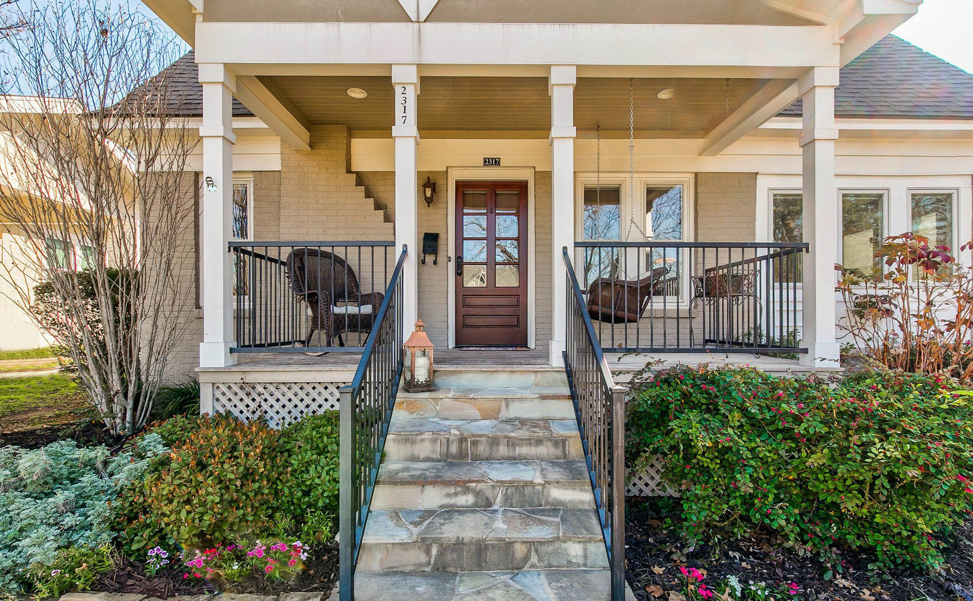 small house front porch with warm cream columns, tan brick, a reall wood front door,stone steps