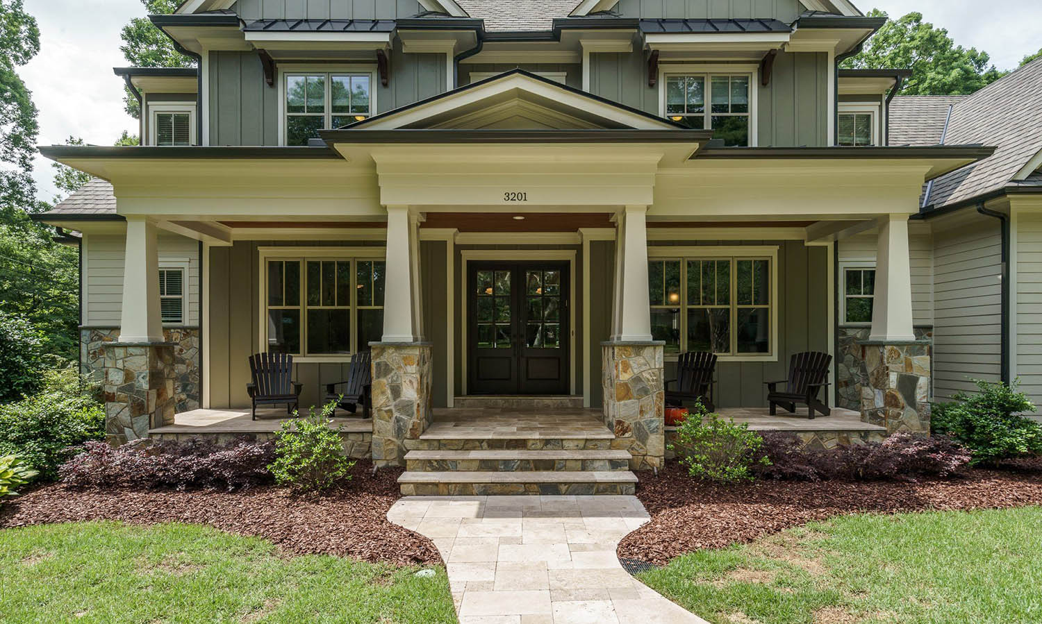 muted gray green vertical siding with white trim and black metal roofing stone veneer wood porch soffit