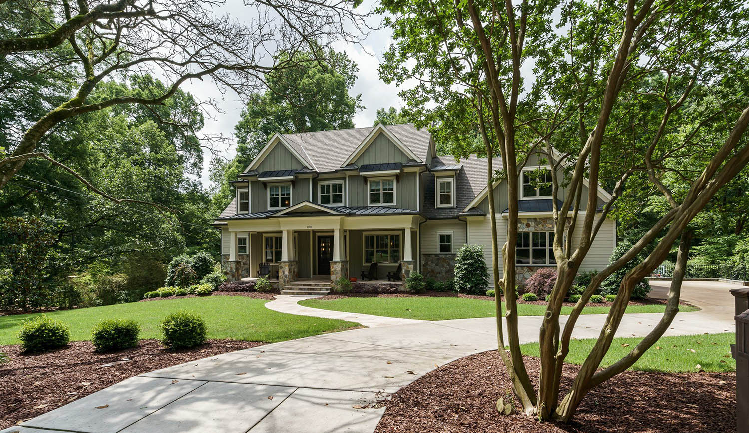 green colored house with white accents, black metal roof, natural stone veneer white trim