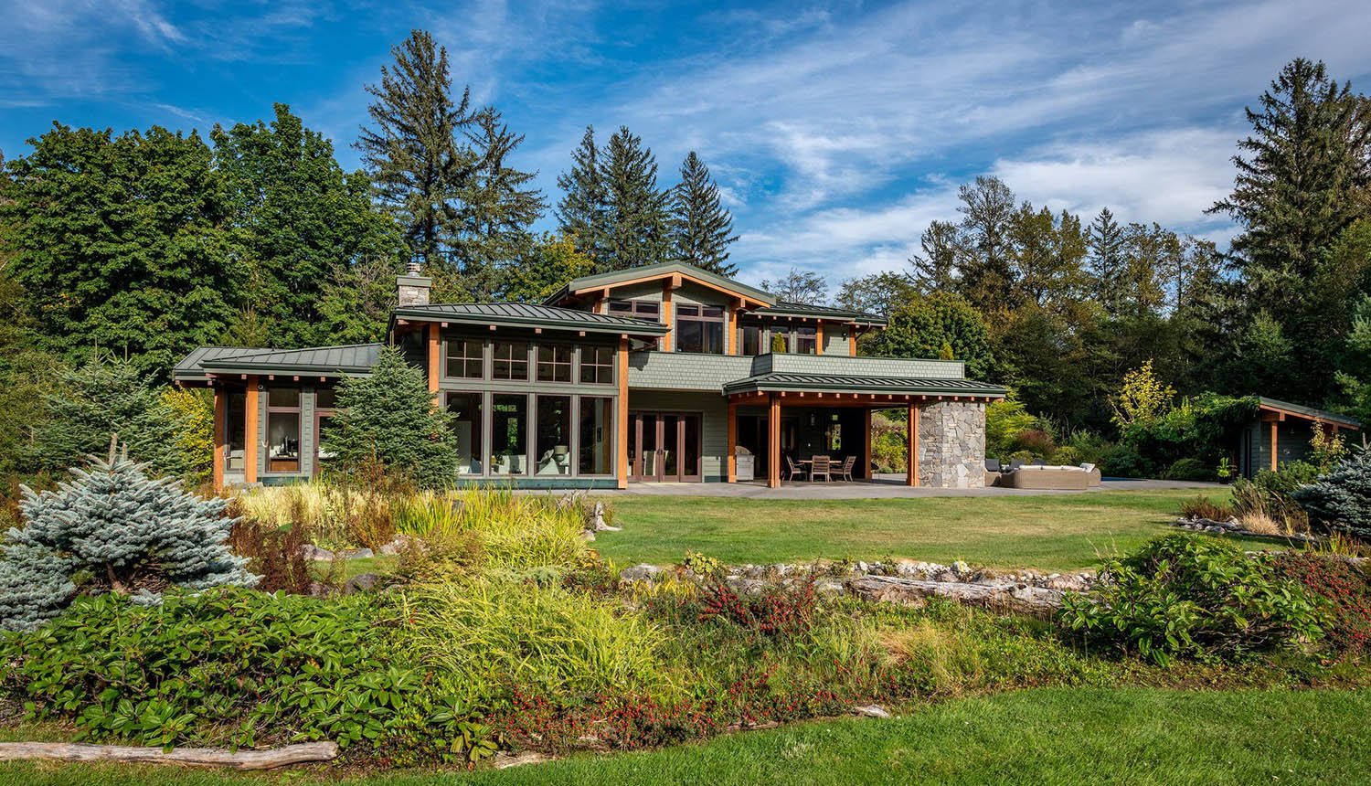 green colored house with wood trim and stone veneer in nature