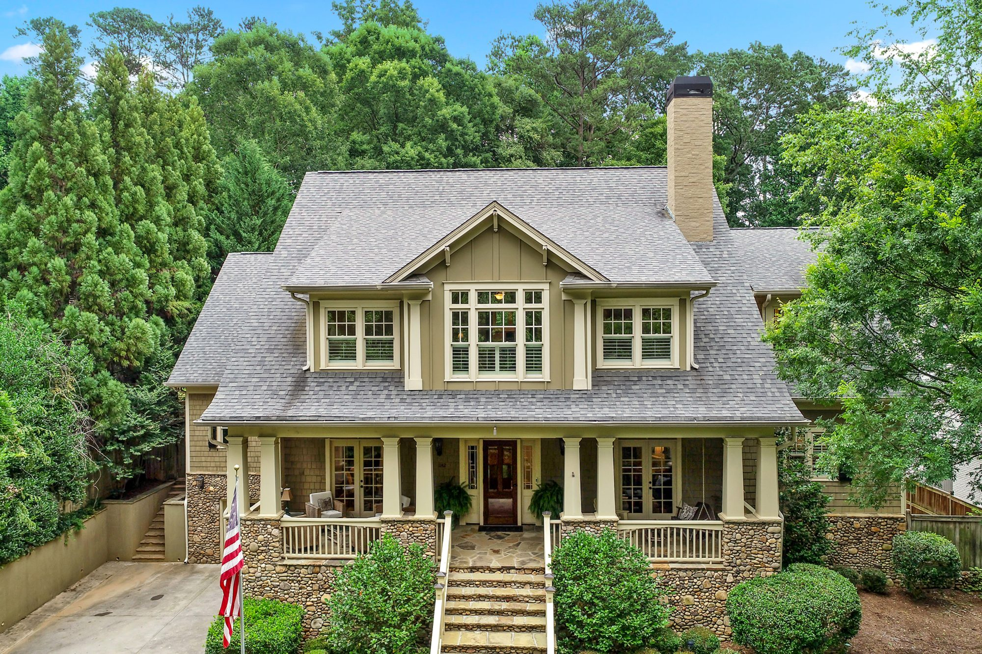 pale olive house color with cream colored trim and columns with a medium brown stained wood front door.