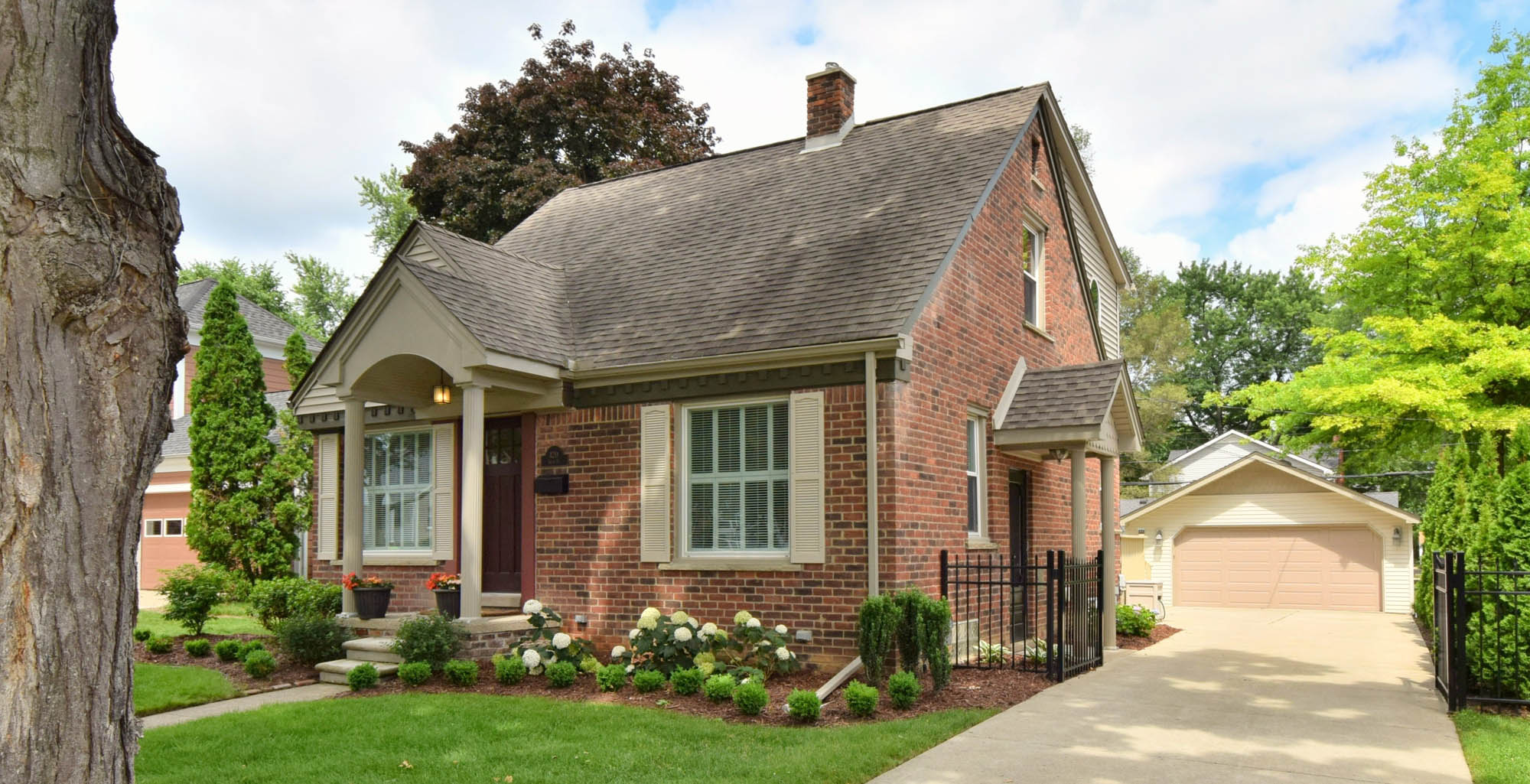 small house color scheme ideas - brick house with tan columns and trim detached garage