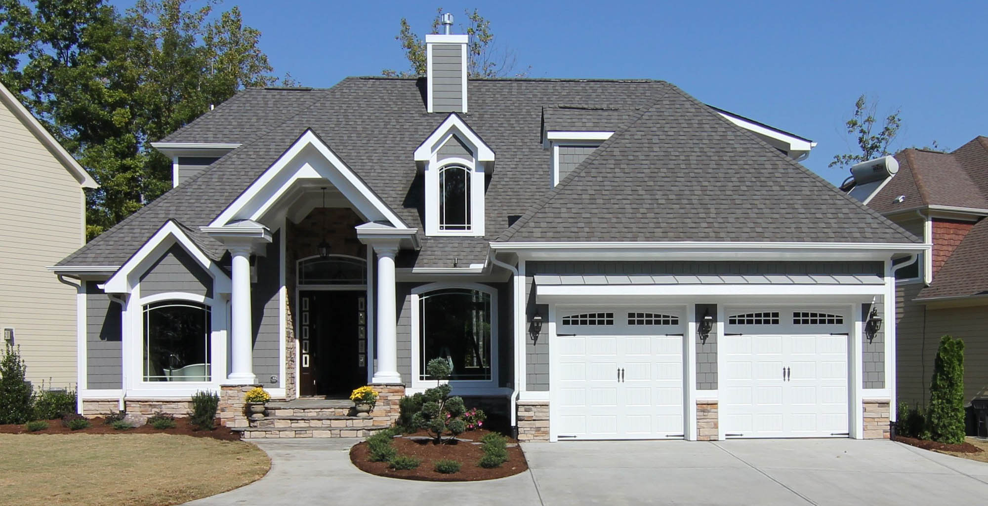 small house color schemes - gray siding with stone metal roof and columns