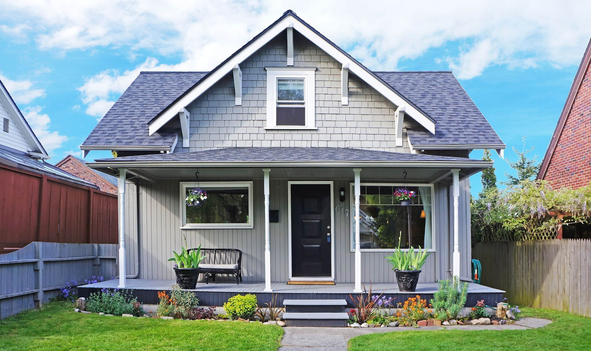 small house siding color ideas - gray small house with white trim and columns dark brown door